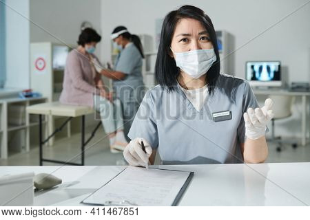 Young Asian clinician in protective workwear sitting by desk and looking at you during medical consultation while her colleague vaccinating patient