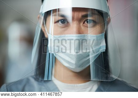 Young Asian serious nurse in uniform and protective workwear standing in front of camera and looking at you through transparent screen