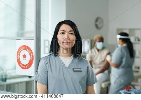 Young contemporary female clinician in uniform standing in front of camera against her colleague vaccinating one of their patients