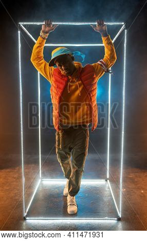 Young stylish rapper poses in illuminated cube