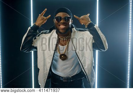 Smiling rapper on the stage with illuminated cube