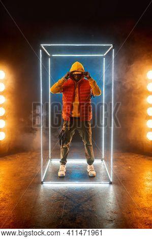 Stylish rapper poses in illuminated cube