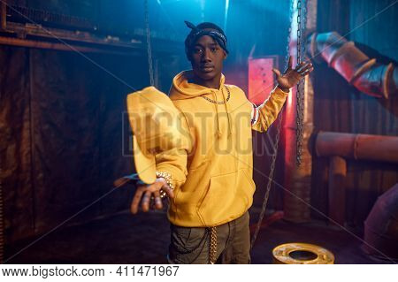 Stylish rapper in yellow hoodie poses in studio