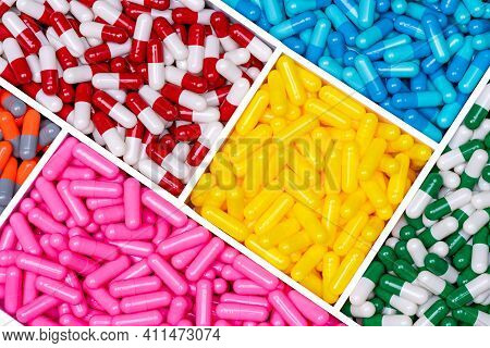 Top View Capsule Pills In Plastic Box. Yellow, Pink, Blue, Red-white, Green-white, And Orange-gray C