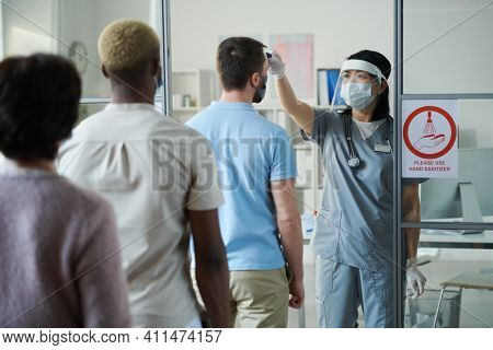 Young female clinician in uniform and protective workwear measuring body temperature of people standing in row in front of her