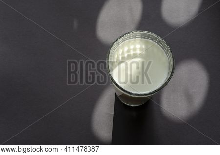 A Glass Of Kefir On A Gray Surface With Shadows. Transparent Glass With A Checkered Pattern. Abstrac