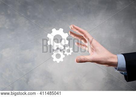 Business Man In Suit Holding Metal Gears And Cogwheels Mechanism Representing Interaction Teamwork C