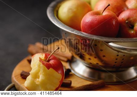 Bitten Apple On Cutting Board With Scattered Cinnamon Sticks On Metallic Bowl Full Of Red Ripe Apple
