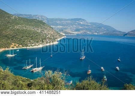 Beautiful scenery of Firnaz bay in Kalkan district, Mediterranean sea coast, Nature of Turkey, Sailing boats on calm turquoise water surrounded by mountains, View from Lycian way hiking trail