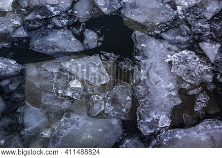 Broken Ice Of Dark Blue Color On The River. Chunks Of Crushed Ice On Dark Water. Abstract Ice Backgr