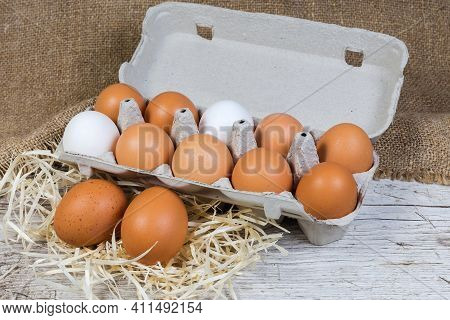 White And Brown Chicken Eggs On A Wood Shavings And In Egg Carton Made Of Recycled Paper Pulp On An