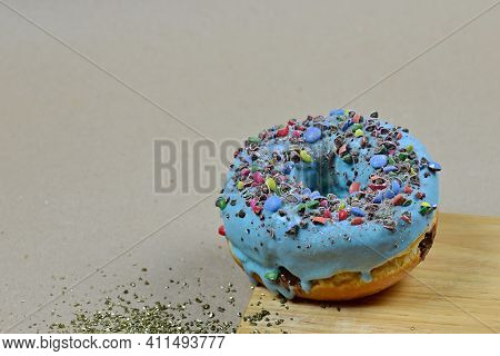 View Of A Sweet Donut With Blue Icing And Crushed Candies. Donut On A Brown Background With A Wooden