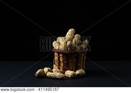 Peanuts On A Black Background. Peanuts In A Small Basket. Peanuts In Shell