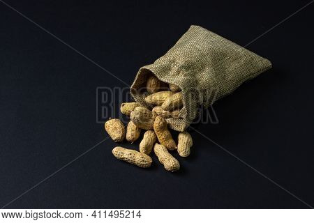 Peanuts On A Black Background. Peanuts In A Small Bag. Peanuts In Shell