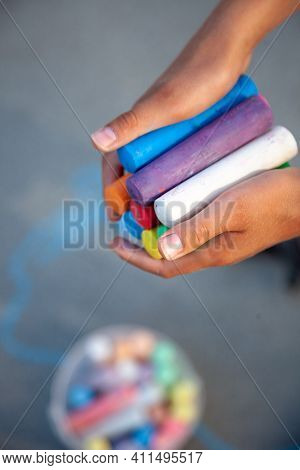 Chalks. Large Multi-colored Crayons In Childrens Hands. The Child Holds The Chalk. Draw On The Stree