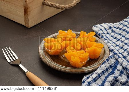 Pinched Gold Egg Yolks Or Khanom Thong Yip In The Thai Language Are Placed On A Plate With Cutlery A