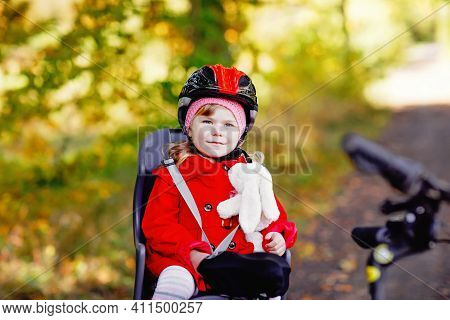 Little Toddler Girl With Security Helmet On Head Sitting In Bike Seat Of Her Mother Or Father Bicycl