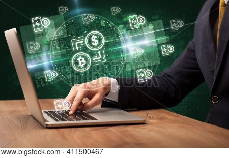 business hand working in stock market with crypto exchange icons coming out from laptop screen
