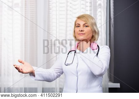 Elderly Female Doctor Wrinkled Her Face And Holds Her Hand Near The Throat, Sore Throat Health Probl