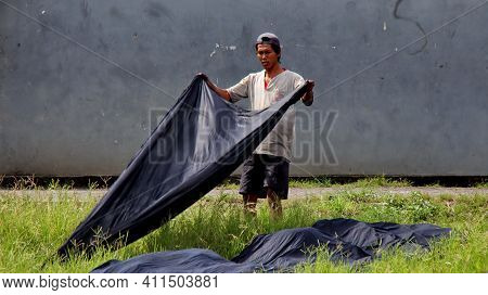 Workers Drying Batik Cloth In The Field, On A Hot Day, Pekalongan, Indonesia, March 8, 2021