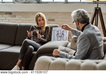 Young Caucasian Woman Discussing Rorschach Test Pictures With Psychotherapist During Session In Offi