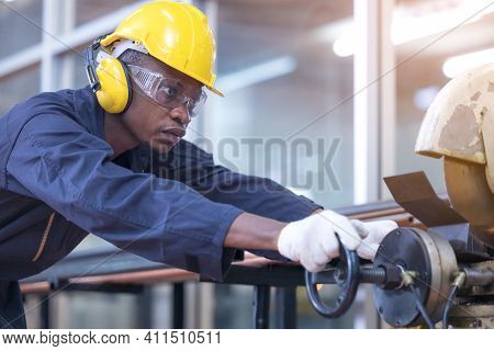 Black Male African American Workers Wear Sound Proof Headphones And Yellow Helmet Working An Iron Cu