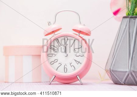 Gentle Pink Alarm Clock Next To A Vase Of Flowers And A Decorative Gift Box In A Scandinavian Style