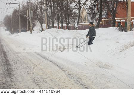 Tula, Russia - February 13, 2020: Man Cleaning Driveway With Scraper From Snow At Winter Morning Aft