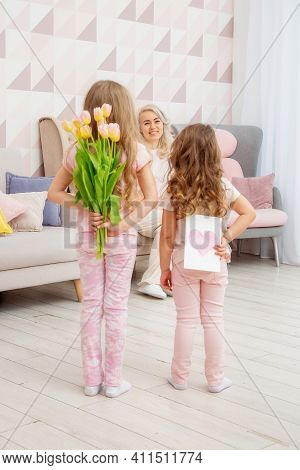 Happy Mother's Day! Child Daughters Congratulate Mom And Give Her A Postcard And Bouquet Of Flowers