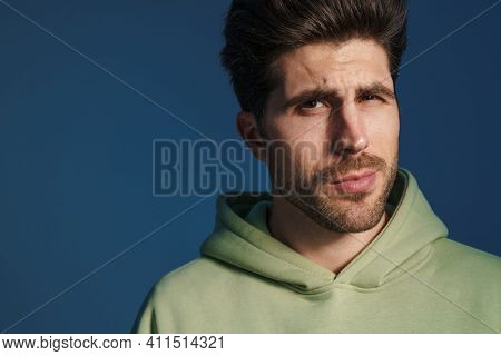 Perplexed handsome man in sportswear posing and looking at camera isolated over blue background