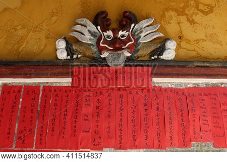 Hoi An, Vietnam, March 8, 2021: Red Colored Papers With Chinese Writing In A Taoist Temple In Hoi An