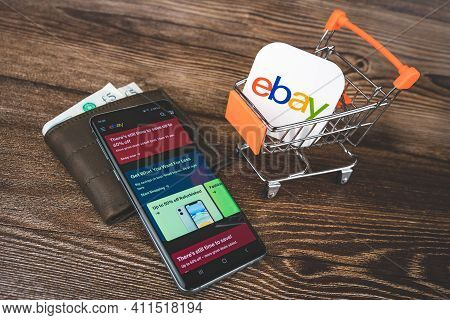 Ebay Logo In Mini Shopping Trolley, Ebay App On Smartphone And Wallet With Pounds Currency. Online S