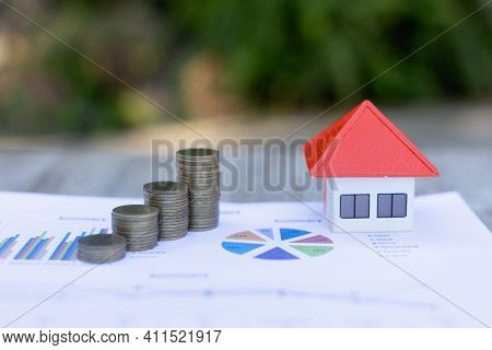 Orange Roof Houses And A Pile Of Coins Are Placed On The Graph. Business Growth Ideas, Economic Char