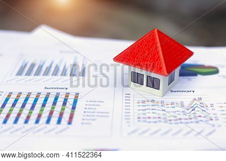 Orange Roof House Placed On The Graph Or Business Data. Concept Of Business Growth Economic Charts,