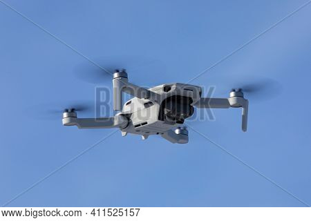 Camera drone hovering in blue sky