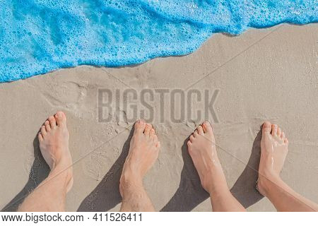 Men's And Women's Feet Stand Next To Each Other On Wet Beach Sand Near Blue Sea Water, Top View.