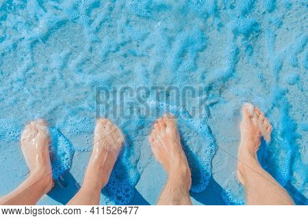 Women's And Men's Feet Stand Side By Side On The Sea Beach In Blue Water, Top View.