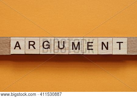 Gray Word Argument Made Of Wooden Square Letters On Brown Background