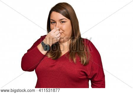 Beautiful brunette plus size woman wearing casual clothes smelling something stinky and disgusting, intolerable smell, holding breath with fingers on nose. bad smell