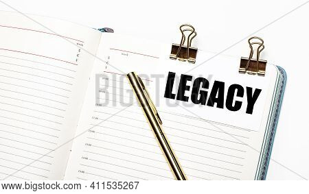 On A Light Background, An Open Notebook, A Sheet Of Paper With Gold Clips And The Text Legacy And A