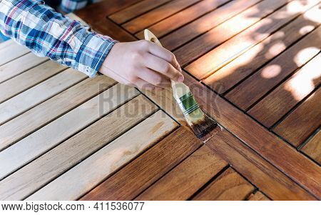 Female Hand Holding A Brush Applying Varnish Paint On A Wooden Garden Table - Painting And Caring Fo