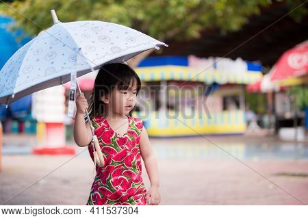 Cute Girl Walked In The Middle Of An Umbrella To Prevent The Drizzle Of Rain. Adorable Kid Wearing A
