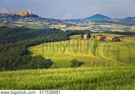 Summer Tuscany Landscape With Cultivated Grain Fields. Famous Vitaleta Chapel And Pienza On The Hill