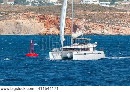 Paros, Greece - 26 September 2020: Catamaran Departing From The Port. Hills With White Traditional B