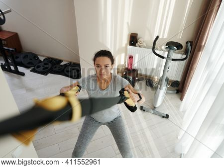 High Angle View Of Athletic Woman Exercising At Home With Fitness Straps. Home Workout Concept