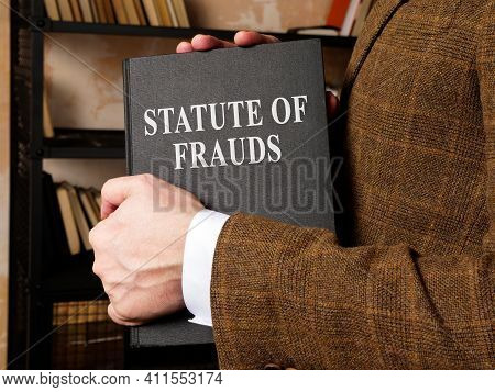 The Lawyer Takes A Statute Of Frauds Book From The Shelf.
