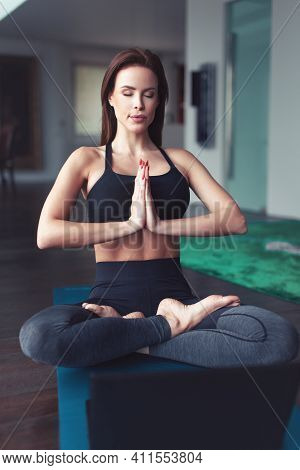 Caucasian Woman Doing Yoga In Lotus Sit At Home, Eyes Closed, Relaxing And Mental Health