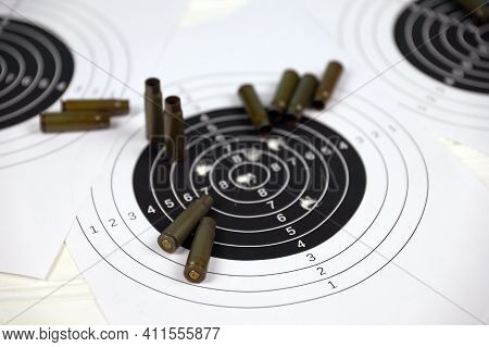 Many Bullets With Shooting Targets On White Table In Shooting Range Polygon. Training For Aiming And