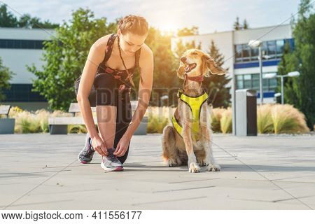 Woman of runner and dog on city street under sunrise sky in morning time. Outdoor walking. Athletic young girl with his dog are running in town.
