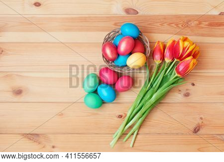 Colorful Easter Eggs In Wicker Basket And Tulip Flowers On Wooden Background. Top View, Copy Space.